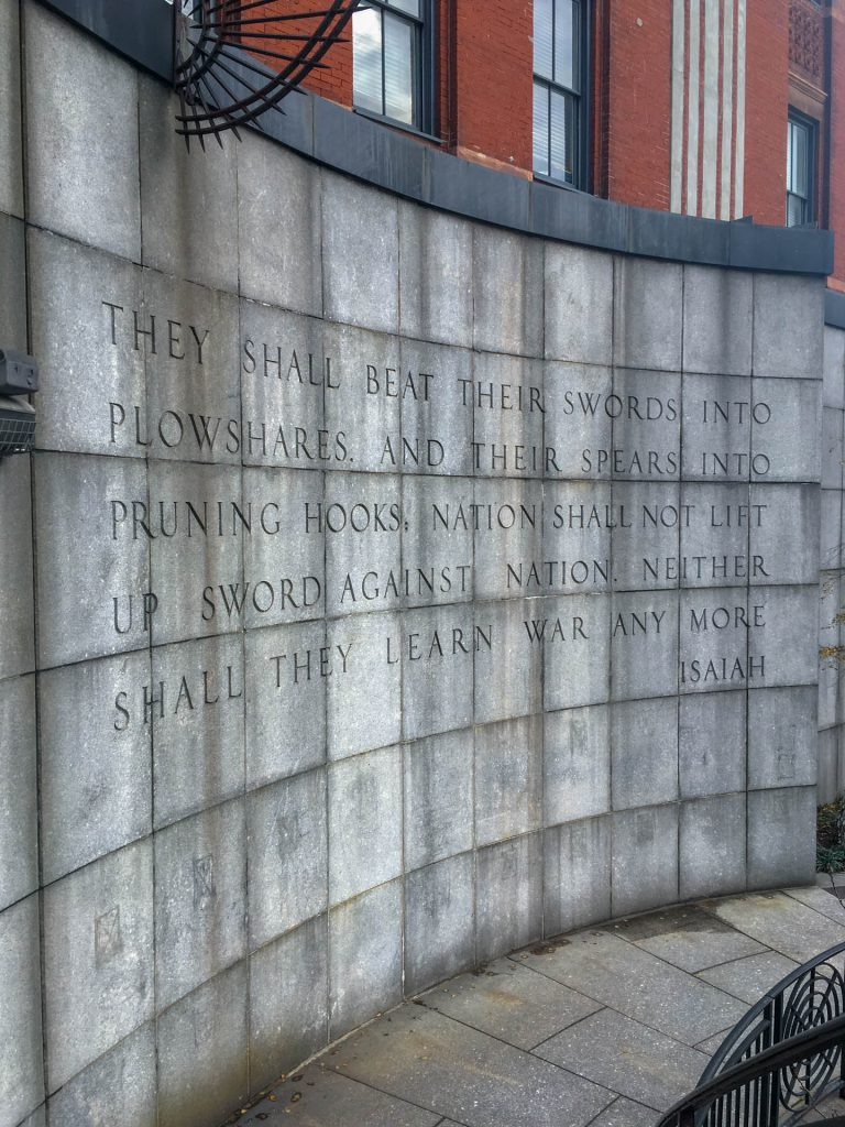 "Stone wall with a quote inscribed that reads, ""They shall beat their swords into plowshares and their spears into running hooks. National shall not lift up sword against nation. Neither shall they learn war any more."" Isaiah"